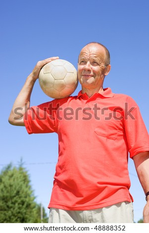 Man holding football on his shoulder - stock photo