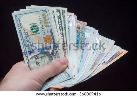 Man holding foreign currencies from various counties.