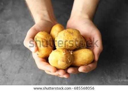Man holding fresh young potatoes on grey background