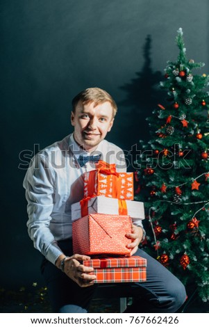man holding giftbox. Handsome male with gift box in hands over christmas tree
