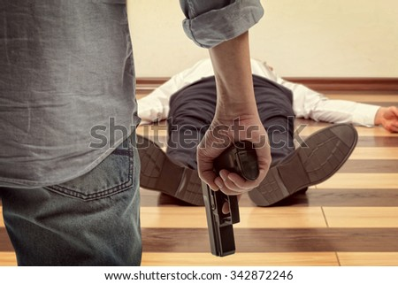 Man holding gun against a corpse background - stock photo