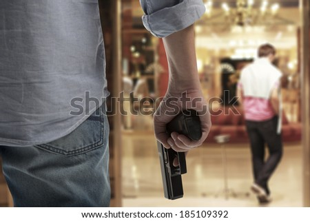 Man Holding Gun against an hotel background - stock photo
