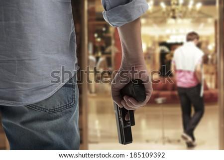 Man Holding Gun against an hotel background - stock photo