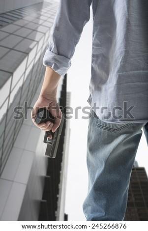 Man holding gun against an skyscraper background  - stock photo