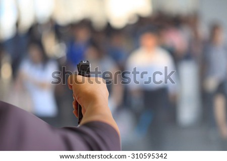 Man holding gun against and crowd background - stock photo