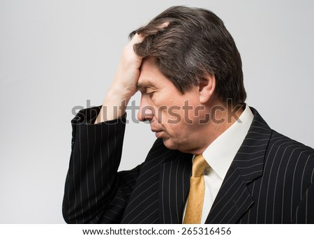 man holding his hand on the head of despair - stock photo