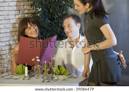man holding his hand on waitress buttocks in a restaurant - stock photo