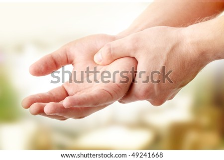 Man holding his hand - pain concept - stock photo