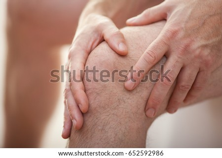 Man holding his knee with two hands