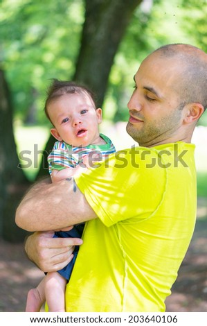 Man holding his son in his arms - stock photo