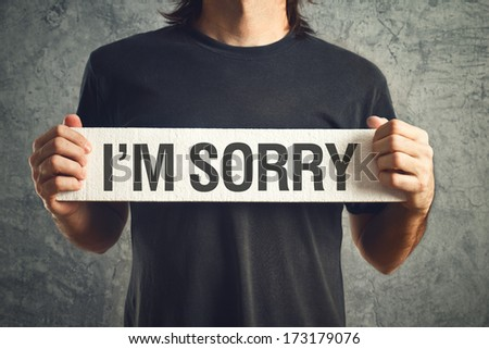 Man holding I am sorry message on white board. remorse concept. - stock photo
