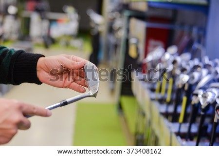 Man holding in hand golf club at a Golf Shop. Closeup photo - stock photo