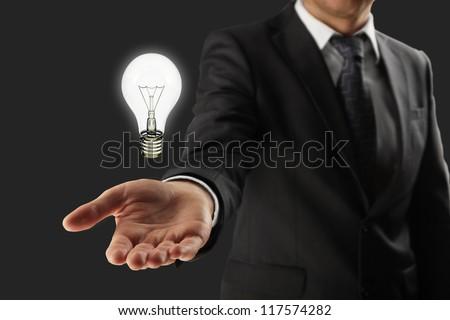 man holding lightbulb in hand - stock photo