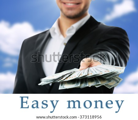 Man holding money on sky background - stock photo