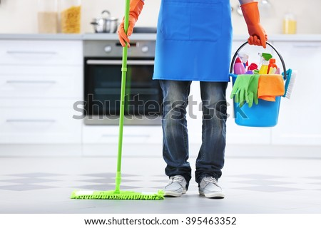 Man holding mop and plastic bucket with brushes, gloves and detergents in the kitchen - stock photo