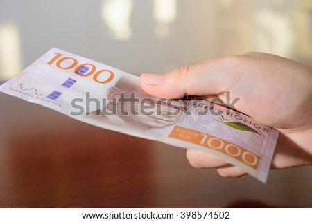 man holding new swedish 1000 bank notes. - stock photo