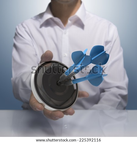 Man holding on black target with three blue darts hitting the center. Concept image for illustration of Marketing and advertising success or self confidence. - stock photo