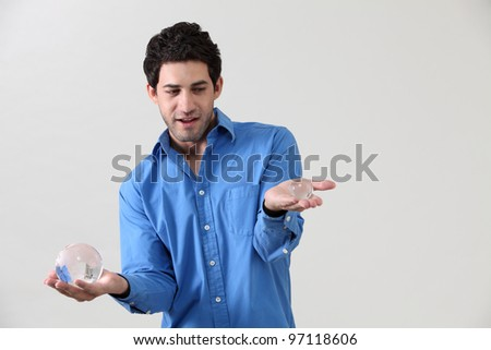 man holding one large and one small globe - stock photo