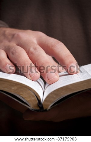 Man holding open Bible in his hands. - stock photo