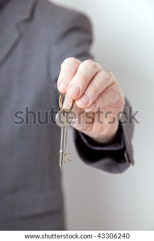 man holding out key - security, hotel or real estate concept - stock photo