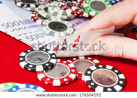 Man holding pair of aces poker hand in front of poker chips stack and euro bills - stock photo