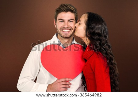 Man holding paper heart and being kissed by girlfriend against shades of brown - stock photo