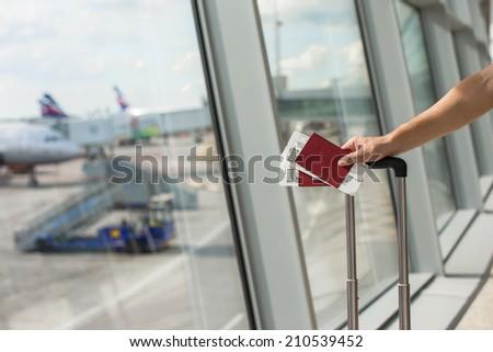 Man holding passports and boarding passport at airport waiting the flight - stock photo