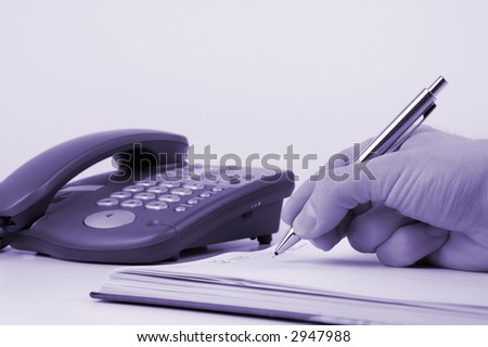 Man holding pen and writing in weekly planner, phone on the background - stock photo