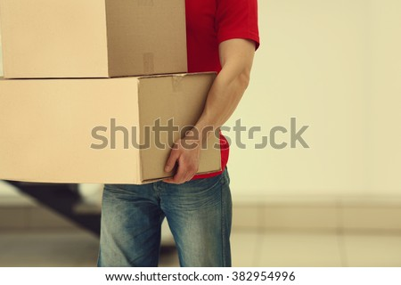 Man holding pile of carton boxes in the room, close up - stock photo