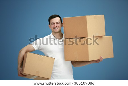 Man holding pile of carton boxes on blue background, close up