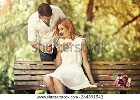 Man holding red box with ring making propose to his girlfriend outdoors. - stock photo