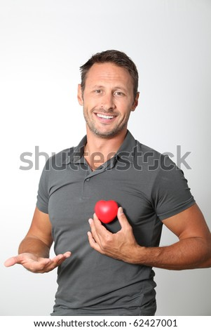 Man holding red heart in his hands - stock photo