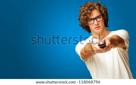 Man Holding Remote Control Isolated On Blue Background - stock photo