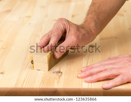 Man holding sanding block on pine floor or table sanding surface - stock photo