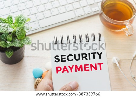 Man holding SECURITY PAYMENT message on book and keyboard with a hot cup of tea, macaroon on the table. Can be attributed to your ad. - stock photo