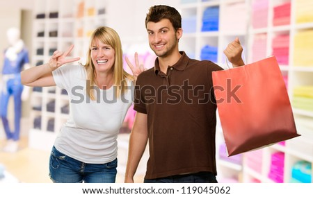 Man Holding Shopping Bag Inf ront Of Happy Woman, Indoors - stock photo