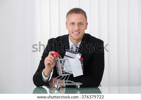 Man Holding Shopping Trolley With Receipt And Calculator - stock photo