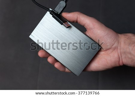 Man holding solid aluminium casing external hard drive with cable