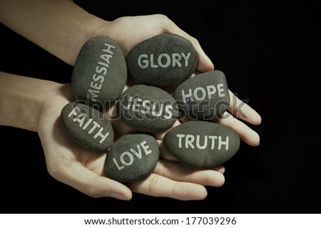 Man holding stones with religion text in palm - stock photo