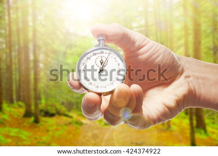 Man holding stopwatch against forest background.Time concept