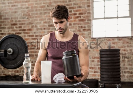 Man holding supplement tin at the gym - stock photo