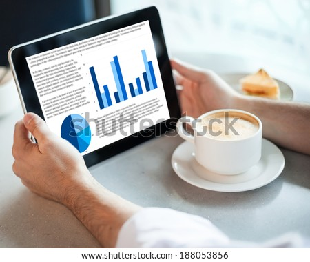 Man holding tablet computer with graphic in cafe - stock photo