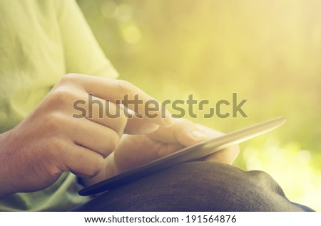 Man holding tablet in the park - stock photo
