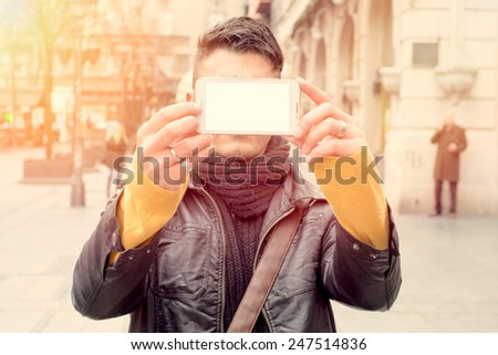 Man holding telephone with blank screen and make selfie - stock photo