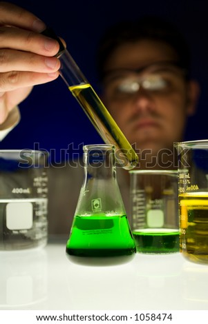 Man holding test tube over light table to view contents. - stock photo