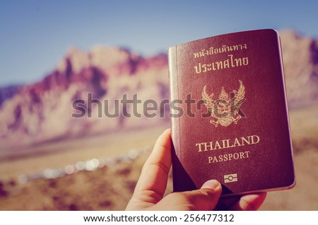 Man holding Thai passport on red rock canyon background - stock photo