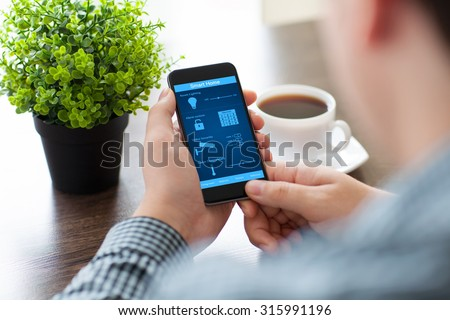 man holding the phone with program smart home on the screen in the office - stock photo