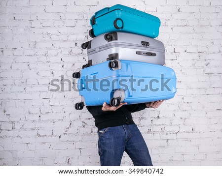 Man holding three heavy suitcases in hand. Travel light. - stock photo