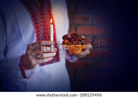 man holding traditional ramadan food at night - stock photo