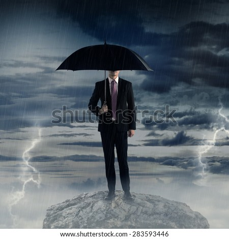 Man holding umbrella standing on the rock with thunder storm weather. Business depression concept